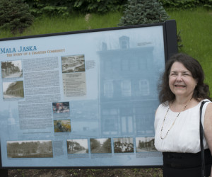 Kathleen (Ribar) Buric, parishioner and former resident of Mala Jaska, admires the neighborhood panel.