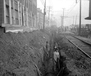 1920 - View of men raising 24-inch cast iron line on E. Ohio St.  715.205056.CP **