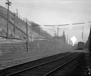 1921 - View of an old stone wall on  E. Ohio Street. St. Nicholas Church is in the background  715.216027.CP **